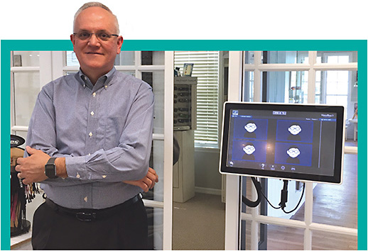 Optician Tom Parrish stands in his optical with the Visioffice 2 from Essilor, one of the many high-tech tools available today to ECPs to expand the patient experience.